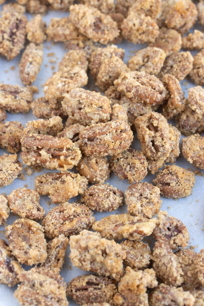 suagred pecans spread out on parchment paper