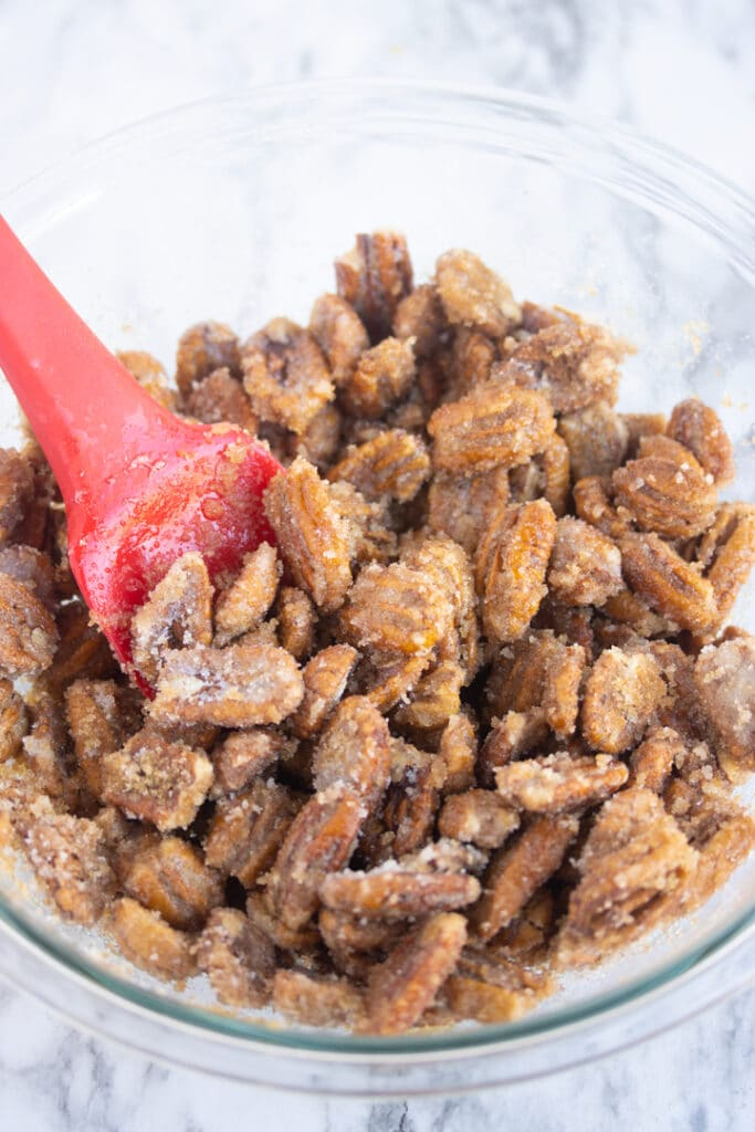 sugar on pecans in bowl with red spatula sticking out