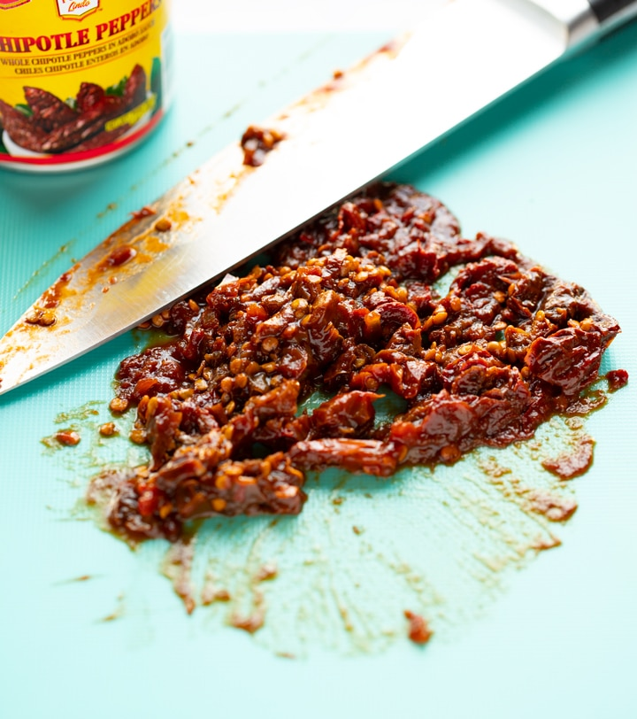 chipotle peppers chopped on cutting mat with knife laying next to it