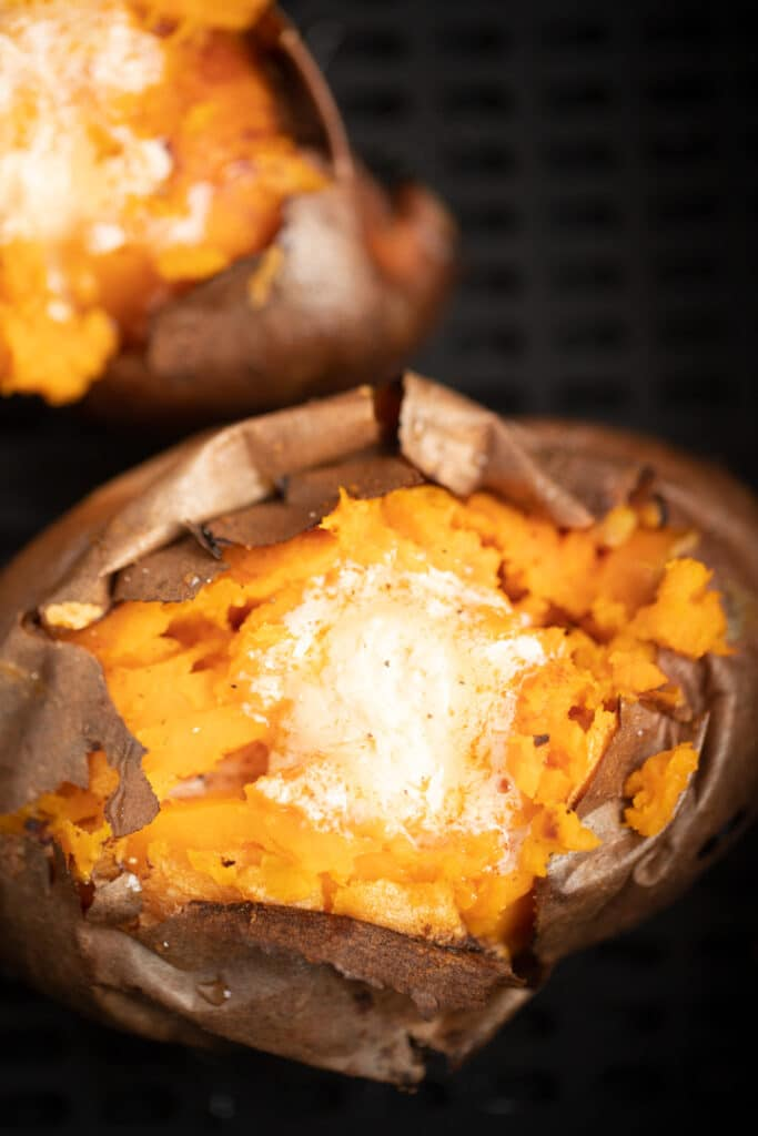 cook air fryer sweet potato in basket opened and topped with hot honey butter