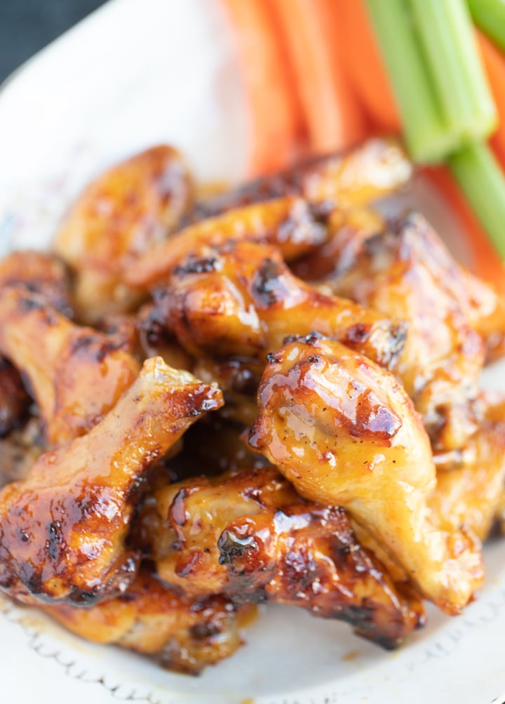 honey mustard wings on a plate with celery and carrots in the back
