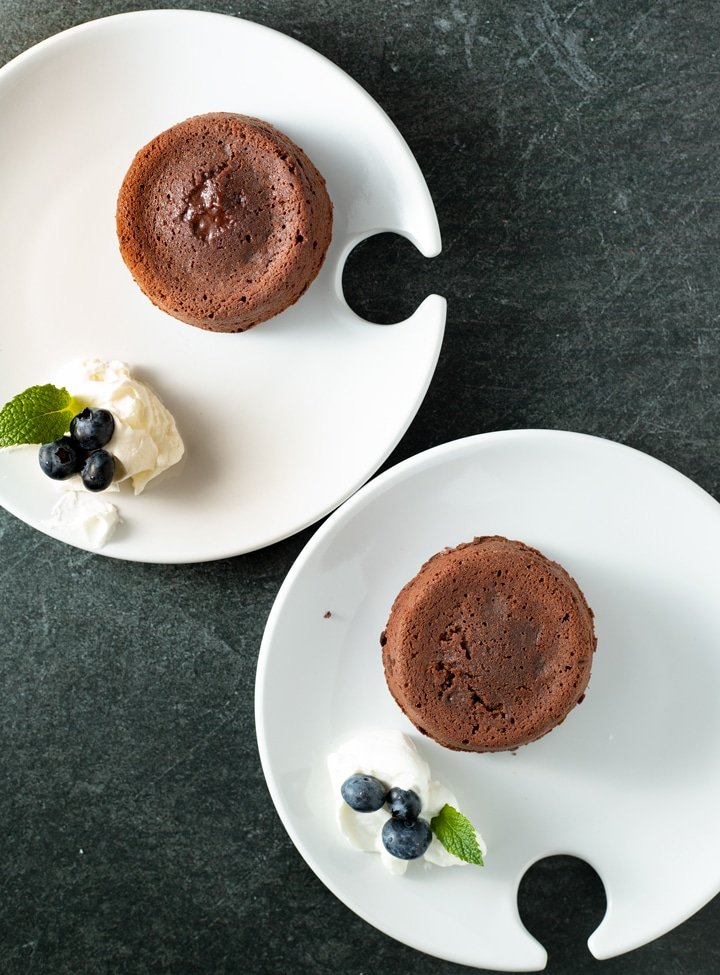 molten lava cakes on little white plates with whipped cream and blueberries and mint on plate