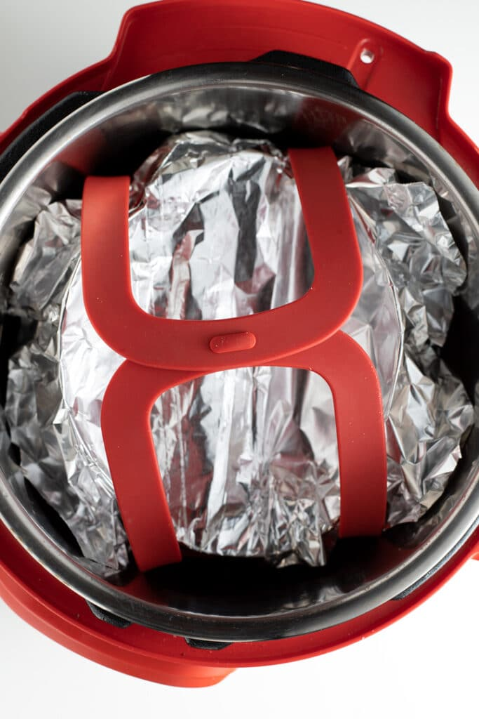 dish covered with foil on bakeware sling inside of instant pot
