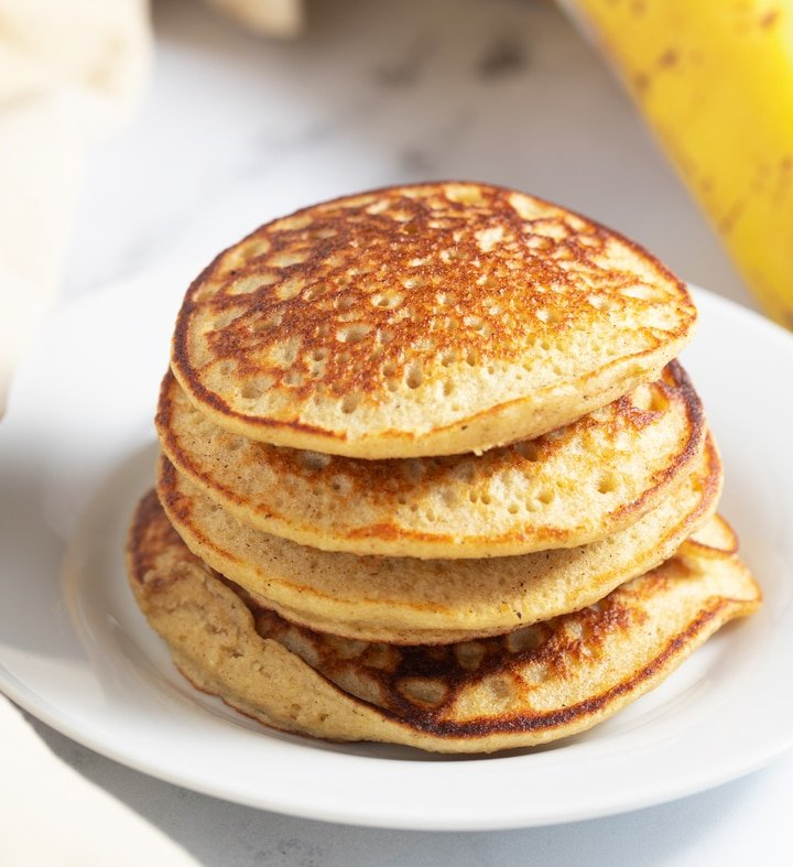 A stack of banana oatmeal pancakes on a white plate