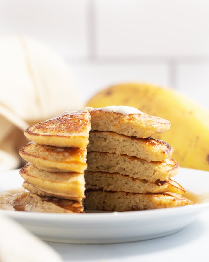 A stack of banana oatmeal pancakes with a slice taken out of them