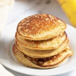 Banana oatmeal pancakes stacked on a white plate