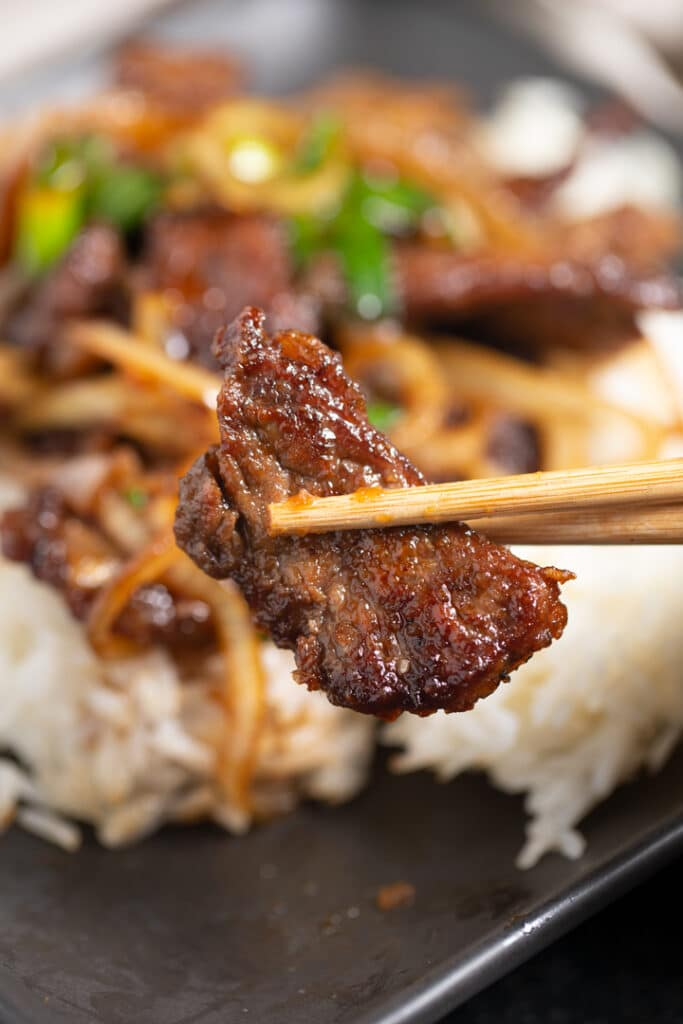 A piece of Mongolian beef held with chopsticks