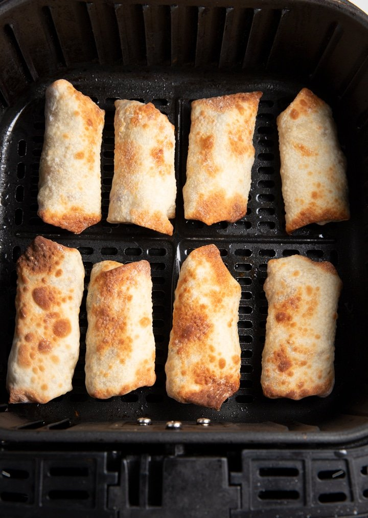 The cooked egg rolls in the air fryer basket