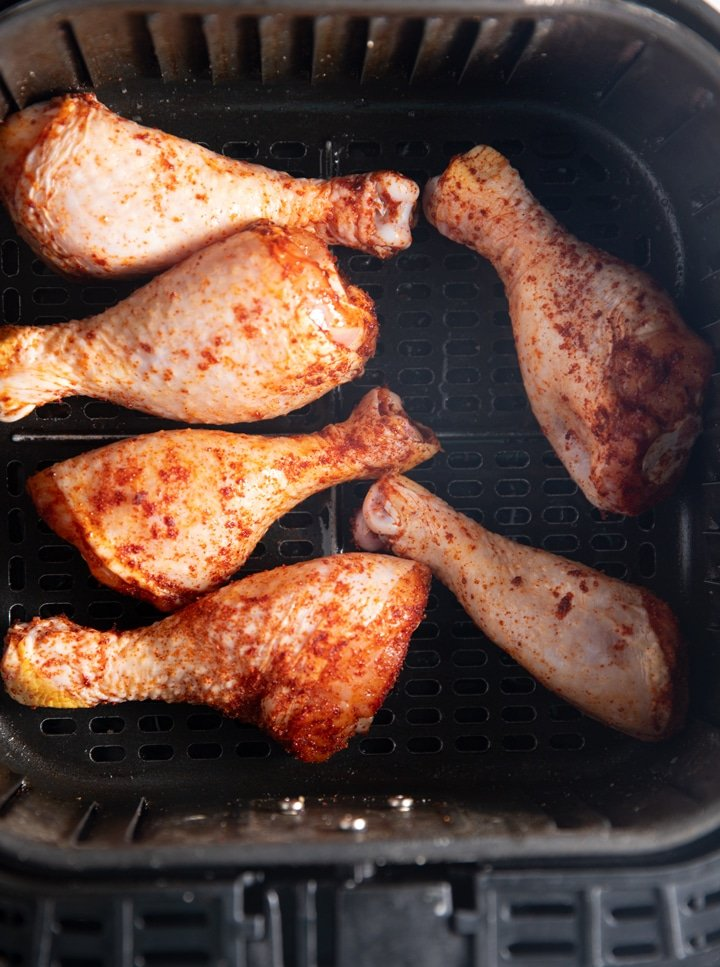 Seasoned chicken legs in the air fryer basket