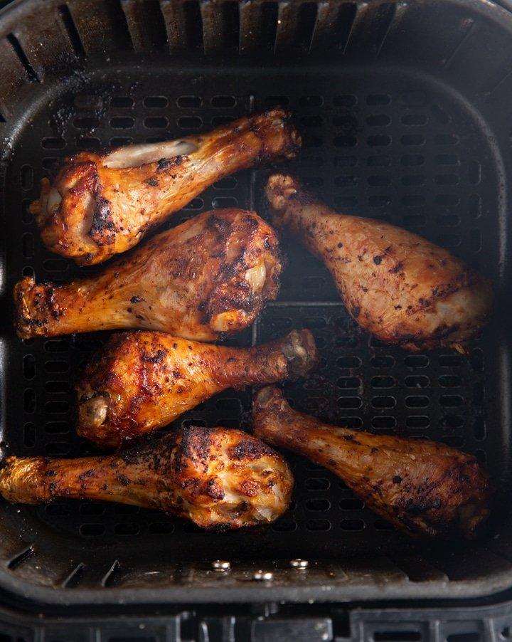 The cooked chicken legs in air fryer basket before being glazed
