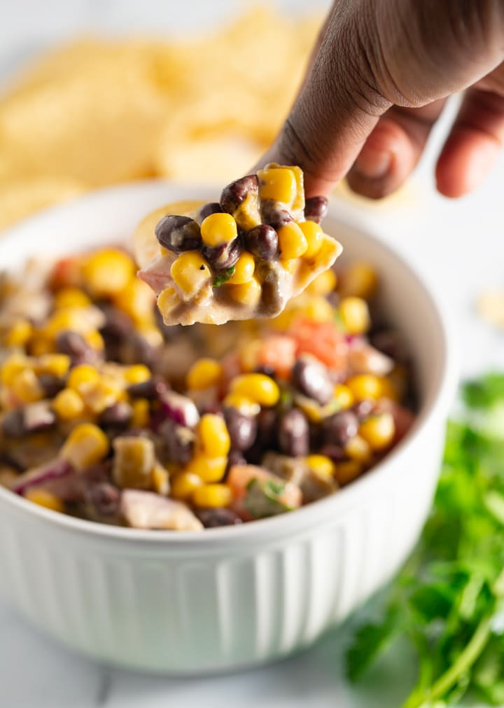 Black bean salsa being scooped with a chip