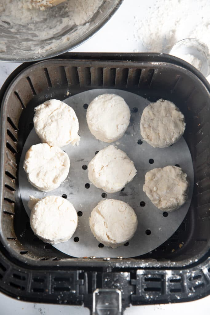 The uncooked biscuits in the air fryer basket
