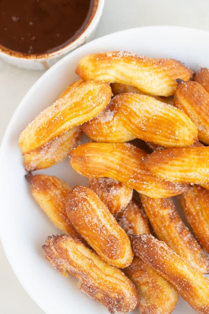 Churros in a white bowl next to chocolate dipping sauce