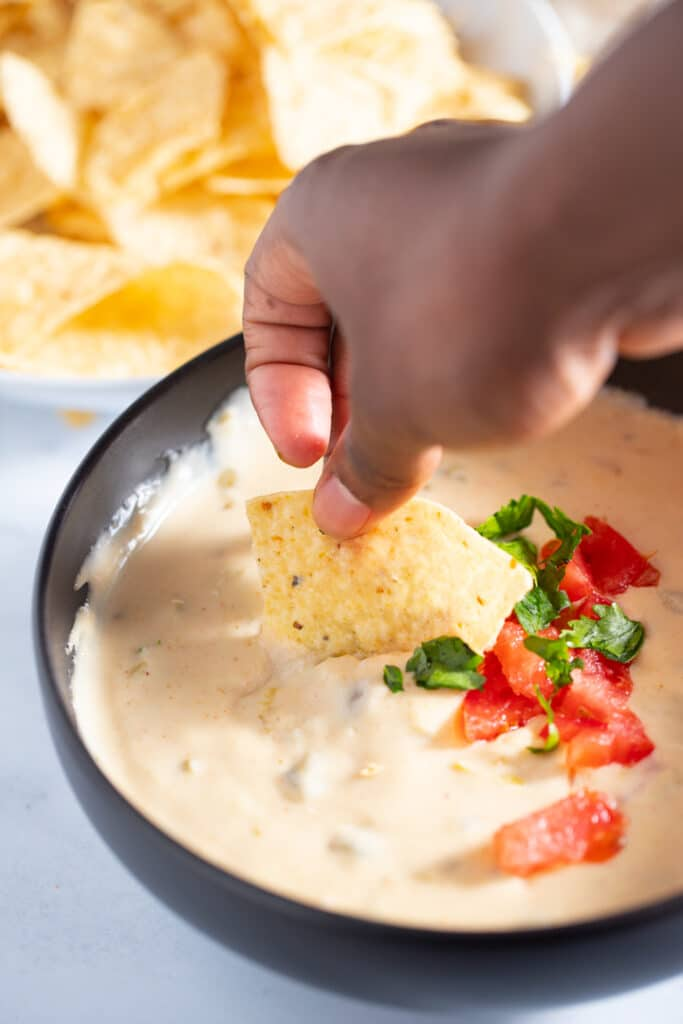 A tortilla being dipped into the queso dip