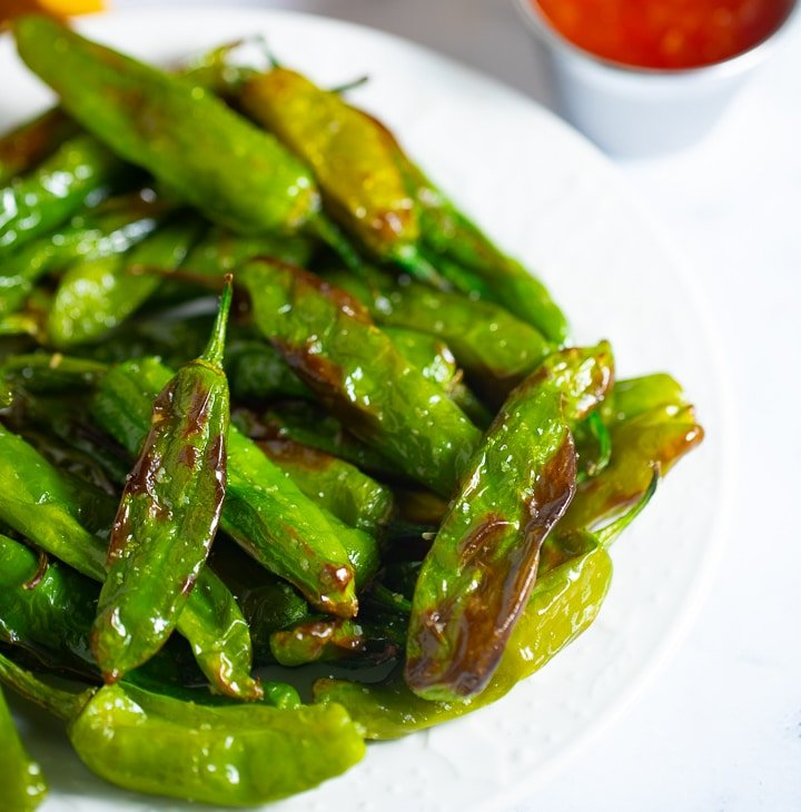 Close up of roasted shishito peppers in a white bowl