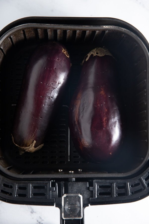 Two eggplants in the air fryer basket