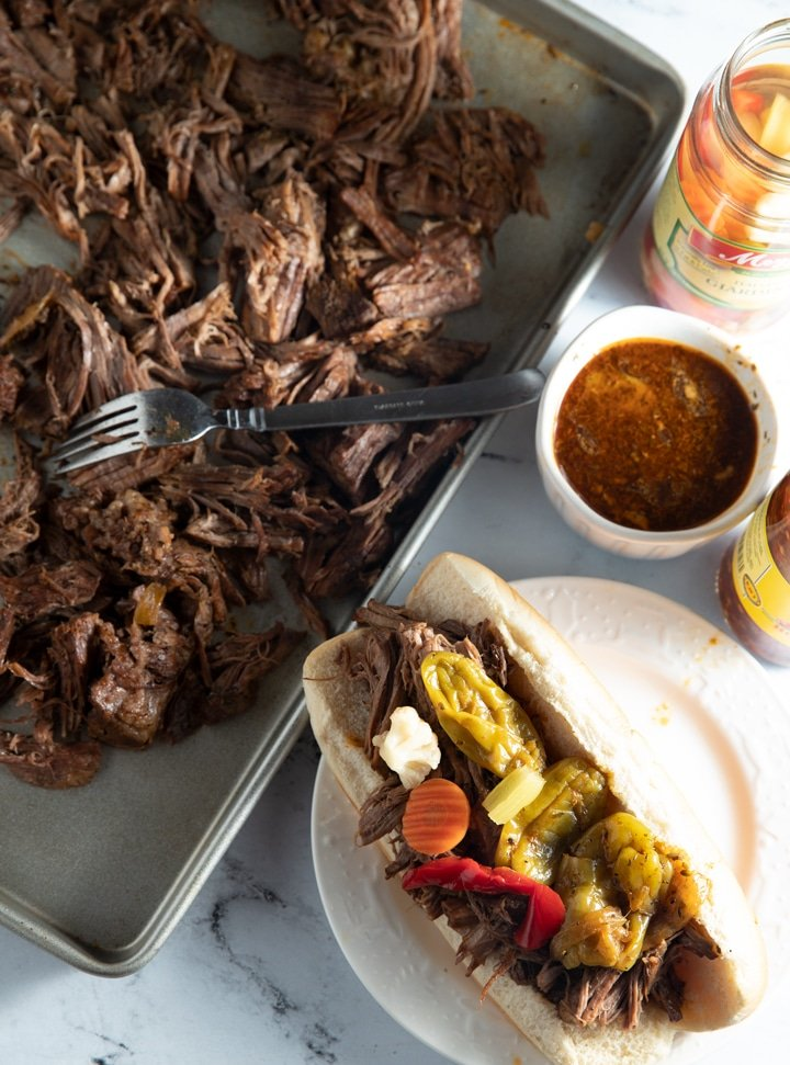 Italian beef on a baking sheet and in a sandwich