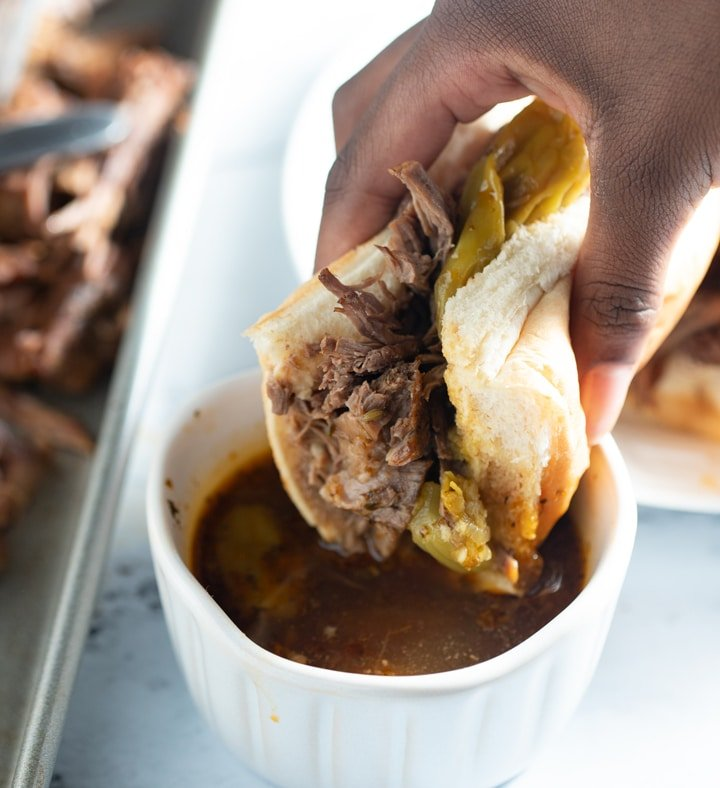 Italian beef in a sandwich being dipped in jus