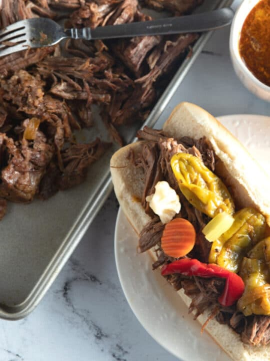 italian beef sandwich on plate next to shredded beef