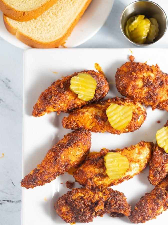 nashville hot chicken tenders on a white plate