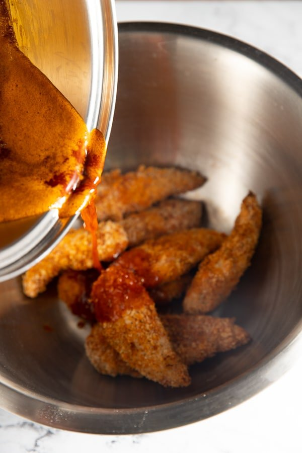 Sauce being poured over the chicken tenders