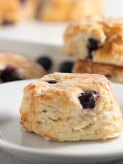 blueberry biscuits on white plate with other biscuits in background