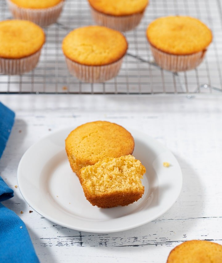 A cornbread muffin broken in half on a white plate