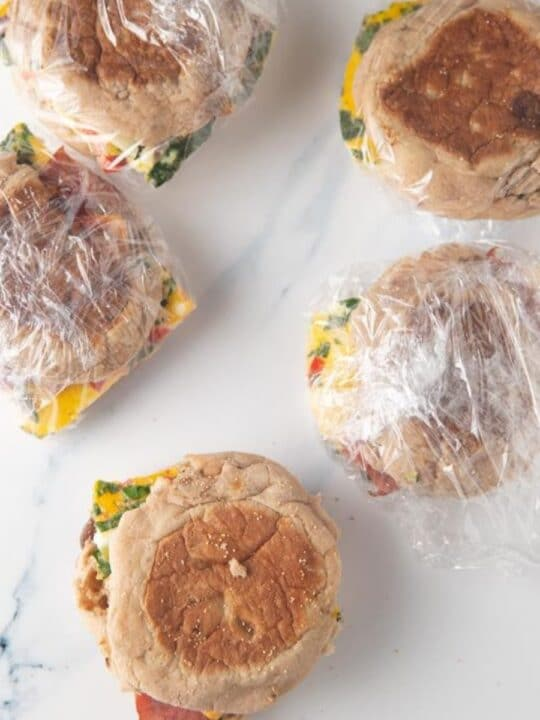 breakfast sandwiches wrapped in plastic wrap on marble with one sandwich unwrapped