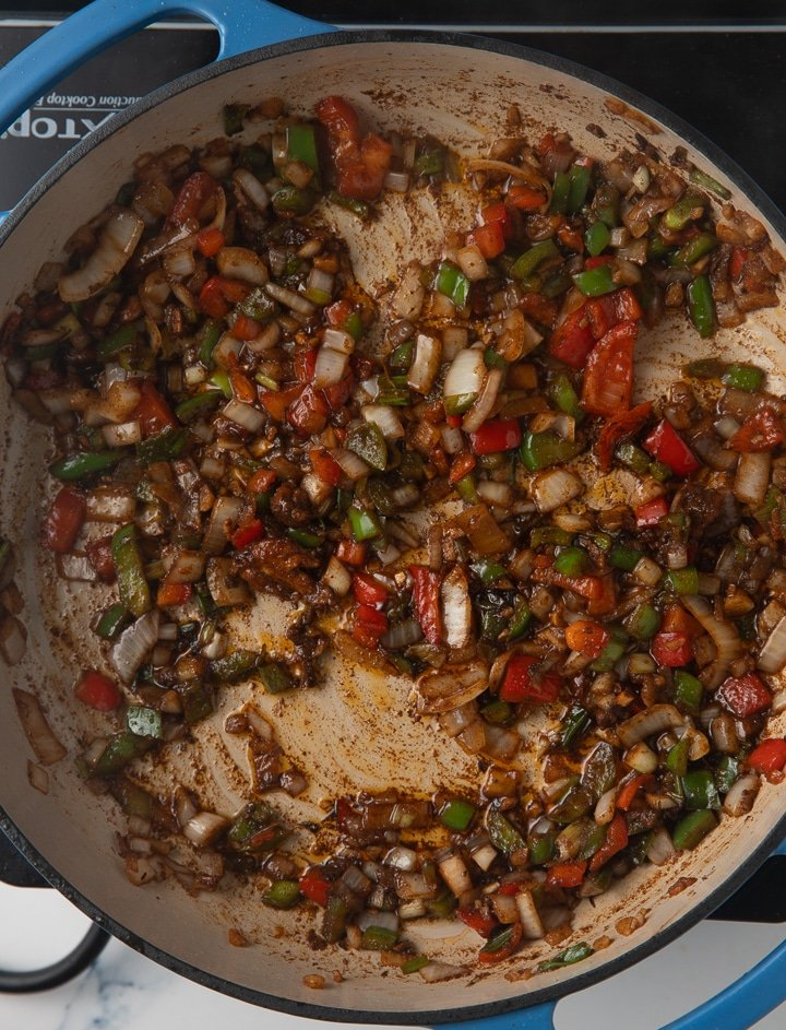 peppers and onions being browned in pan