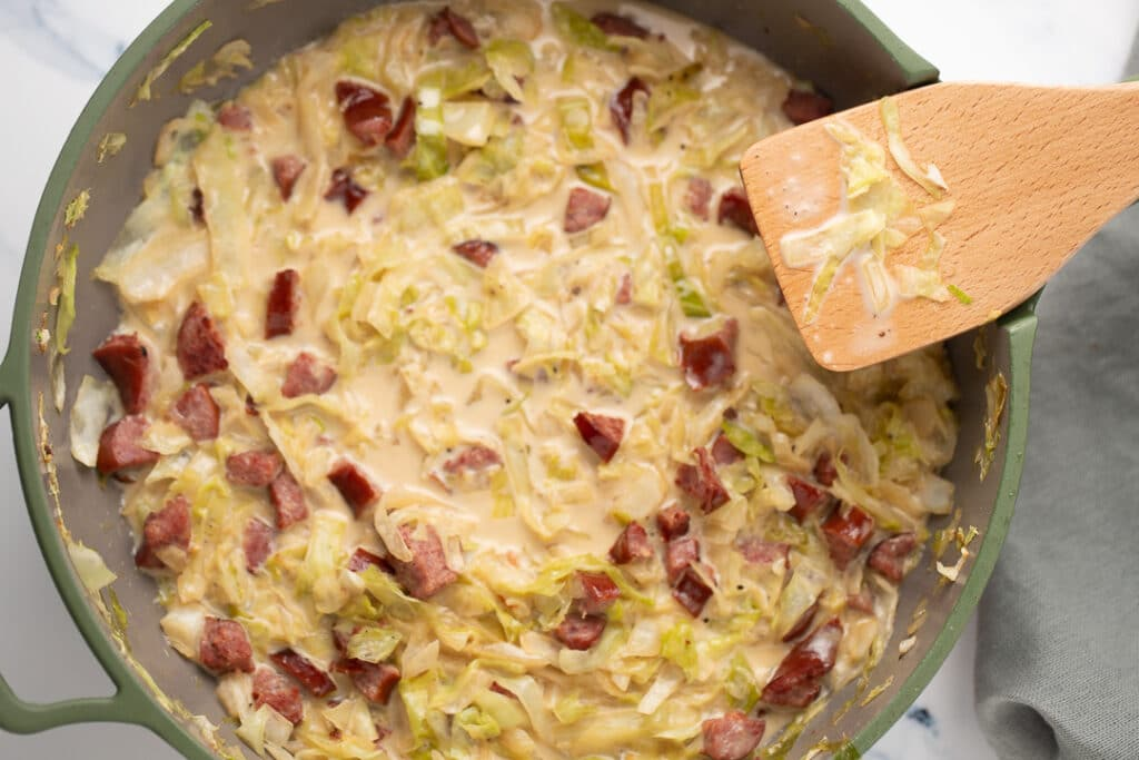 Overhead shot of creamed cabbage and sausage in a skillet with a wooden spatula
