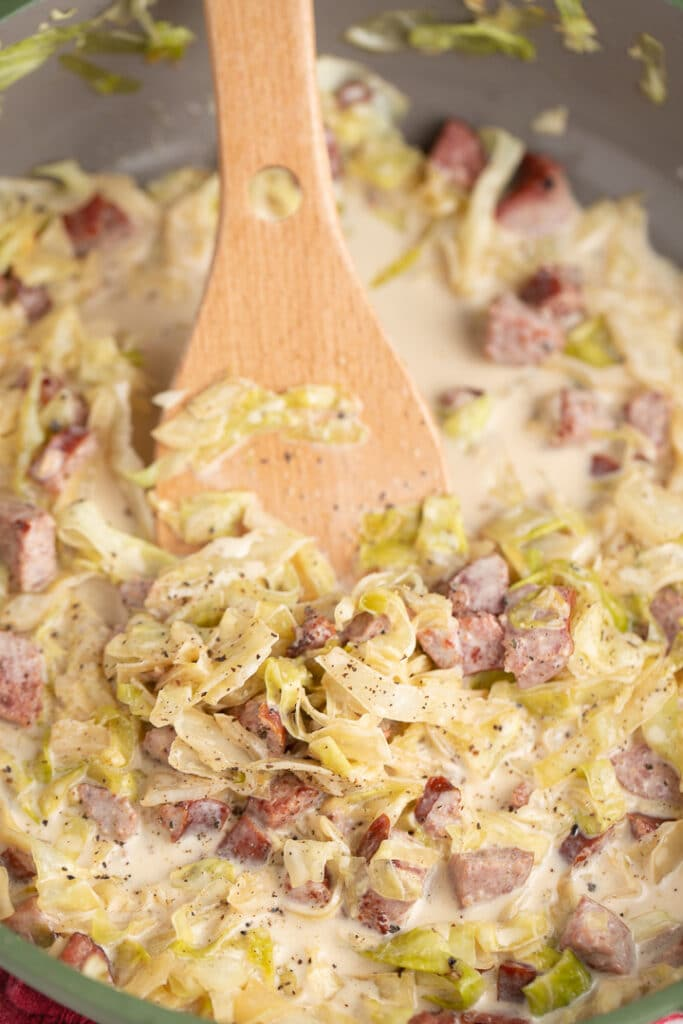 cabbage in skillet with wooden spoon sticking out