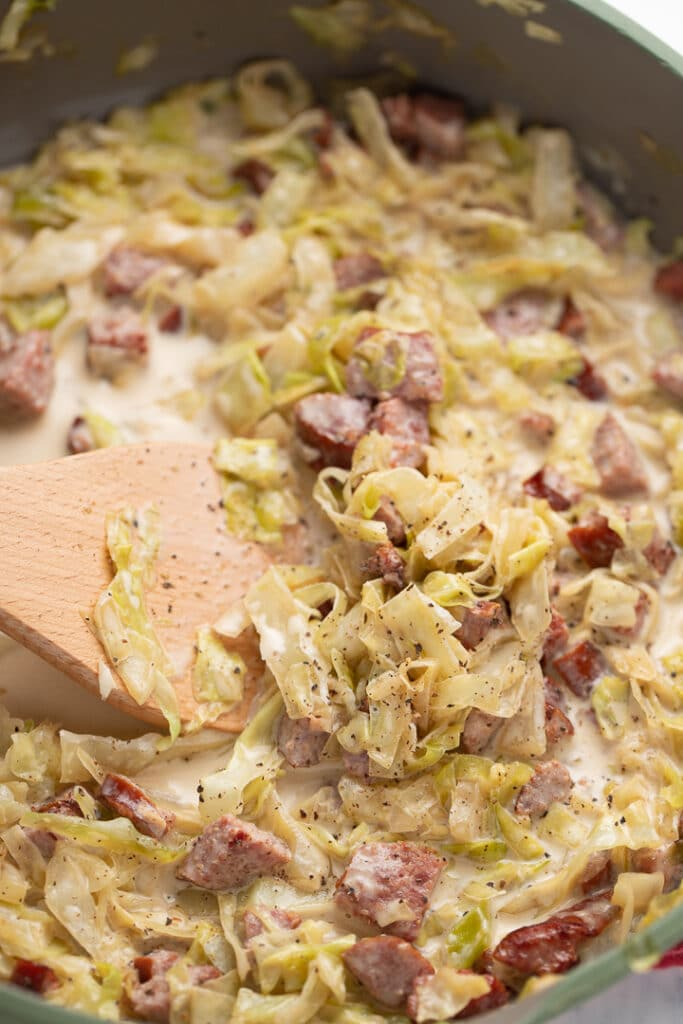 Stirring the creamed cabbage with a wooden spatula