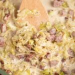 creamed cabbage in skillet with spatula moving the food