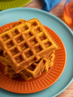 Pumpkin waffles stacked on a plate