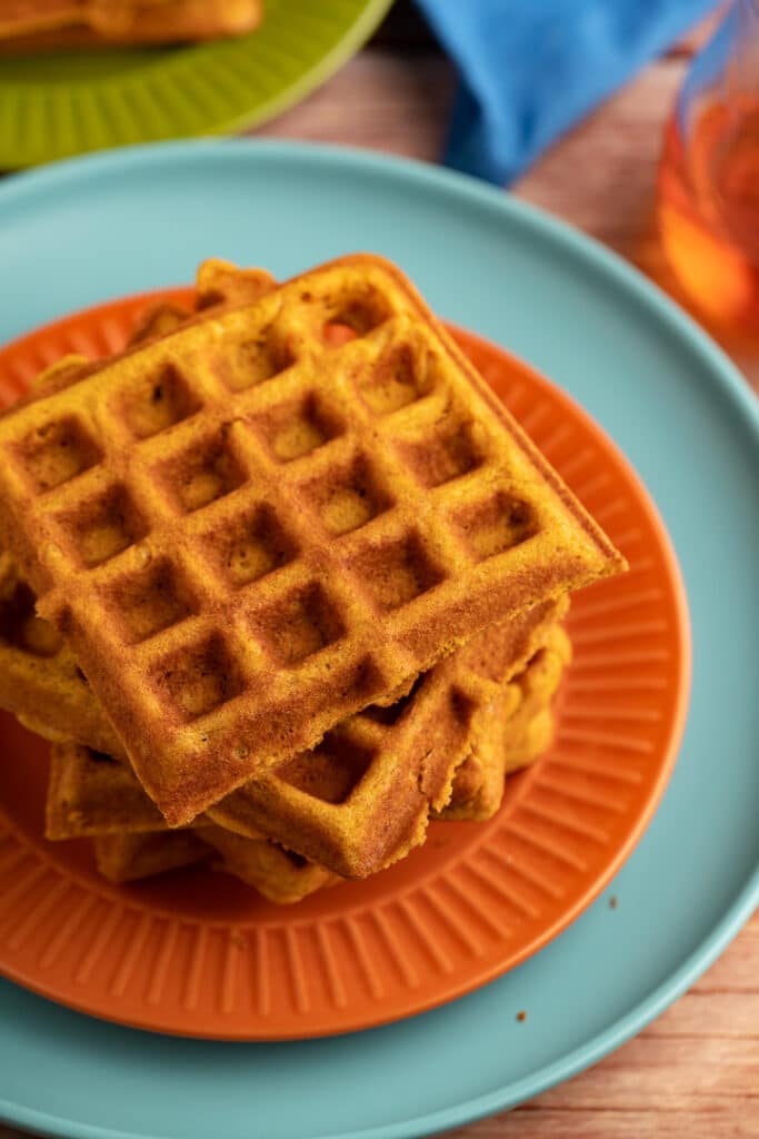 pumpkin waffles stacked on top of each other on orange and teal plate