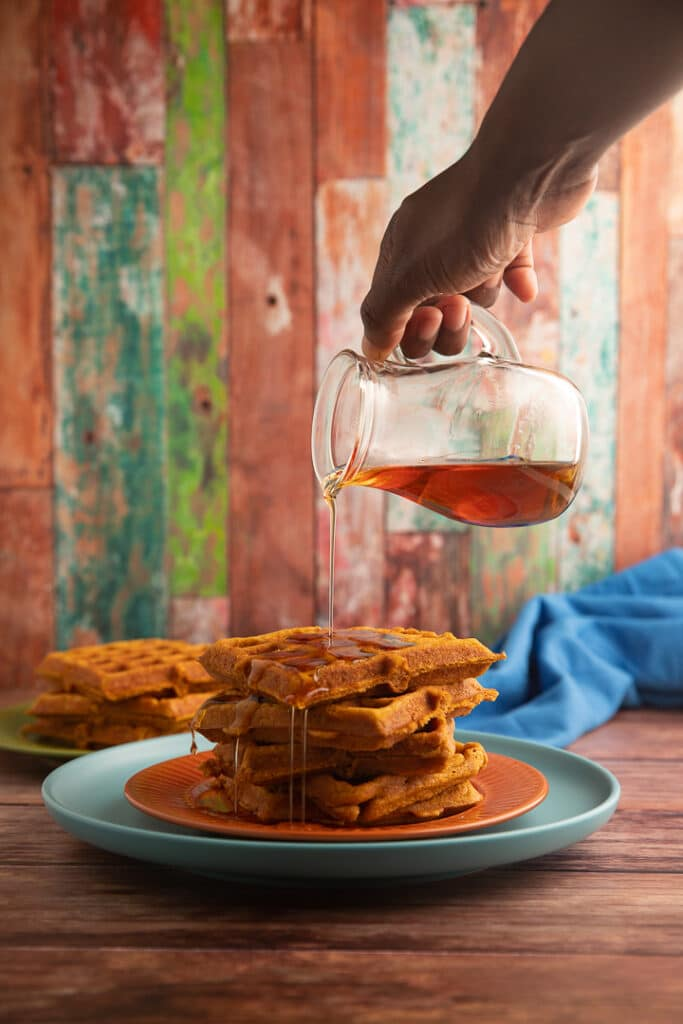 Pouring syrup over stacked waffles