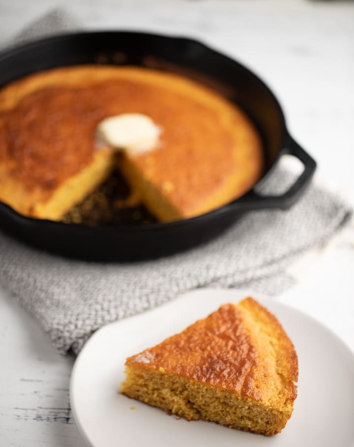 The cornbread in a skillet and a sliced served on a plate