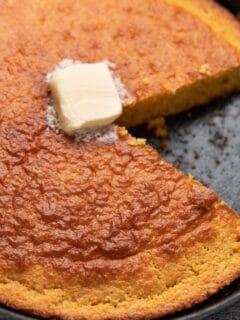cornbread with slice cut from it and butter on top