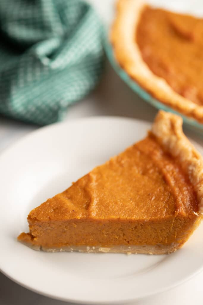 southern sweet potato pie on white plate with pie in background