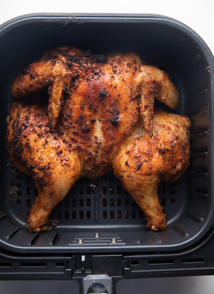 A cooked spatchcok chicken in an air fryer basket