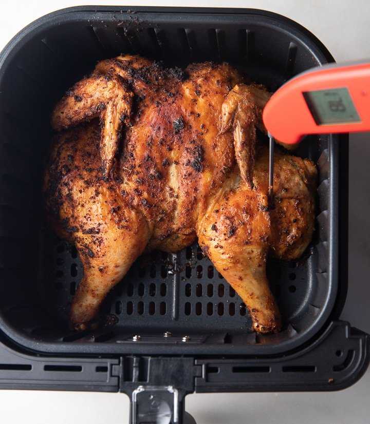 Using an instant read thermometer to check if the chicken is cooked
