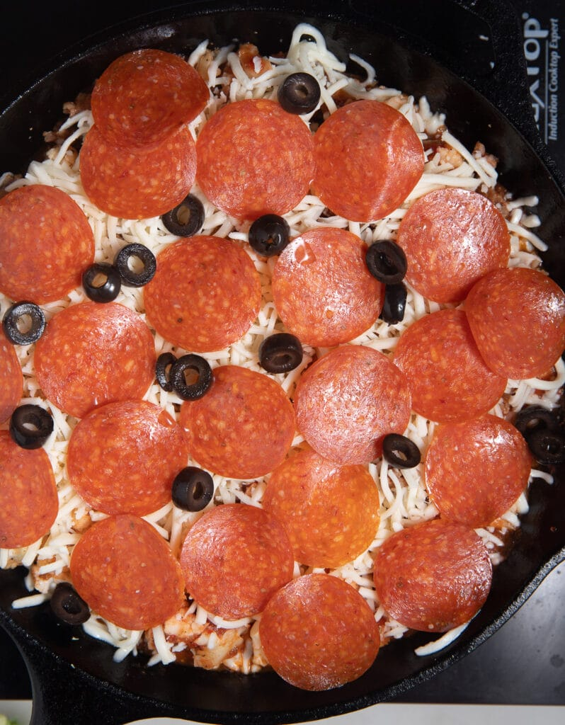 Pepperoni and olives laid on top of the cauliflower.