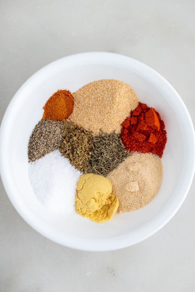 The spices for the seasoning in a white bowl