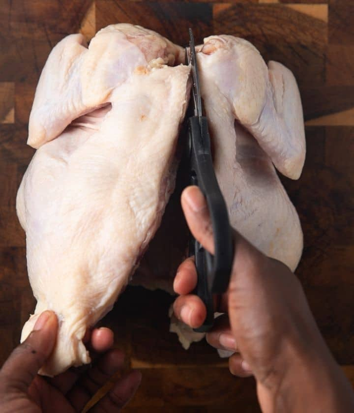 scissors cutting along the backbone of a whole chicken