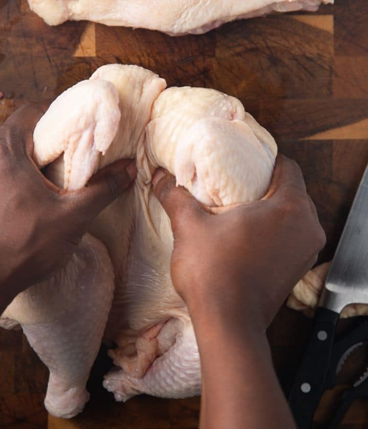 two hands pulling the breast of the chicken apart