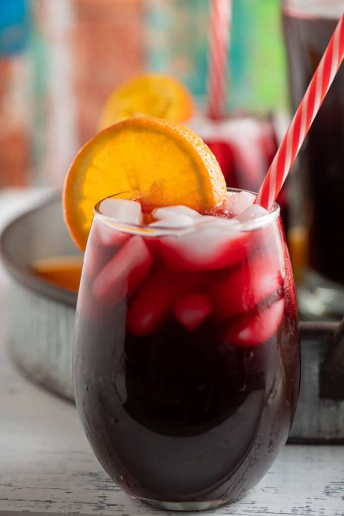 An orange slice garnishing a glass of Jamaican sorrel drink