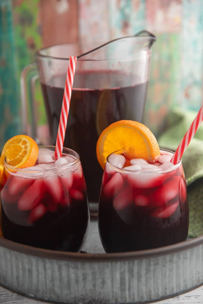 Two glasses of sorrel drink garnished with orange slices