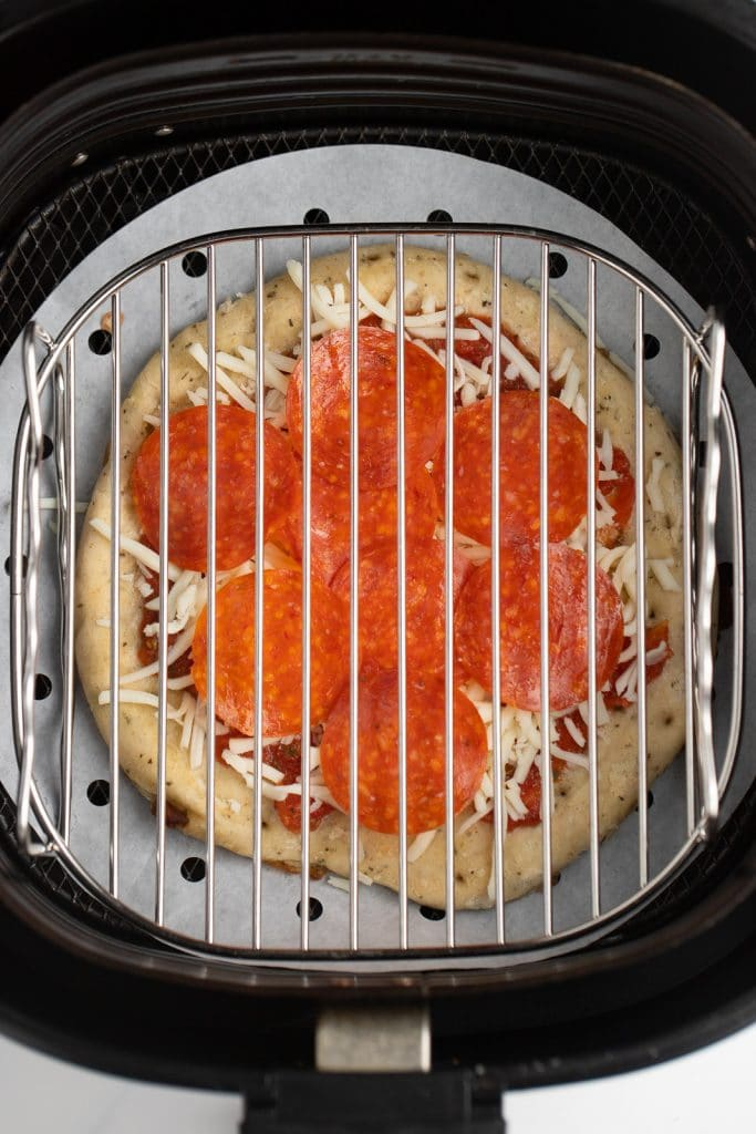 The uncooked pizza in the air fryer basket.