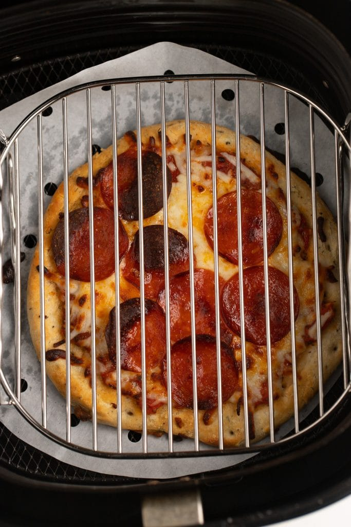 The cooked pizza in the air fryer basket with a rack over the top.