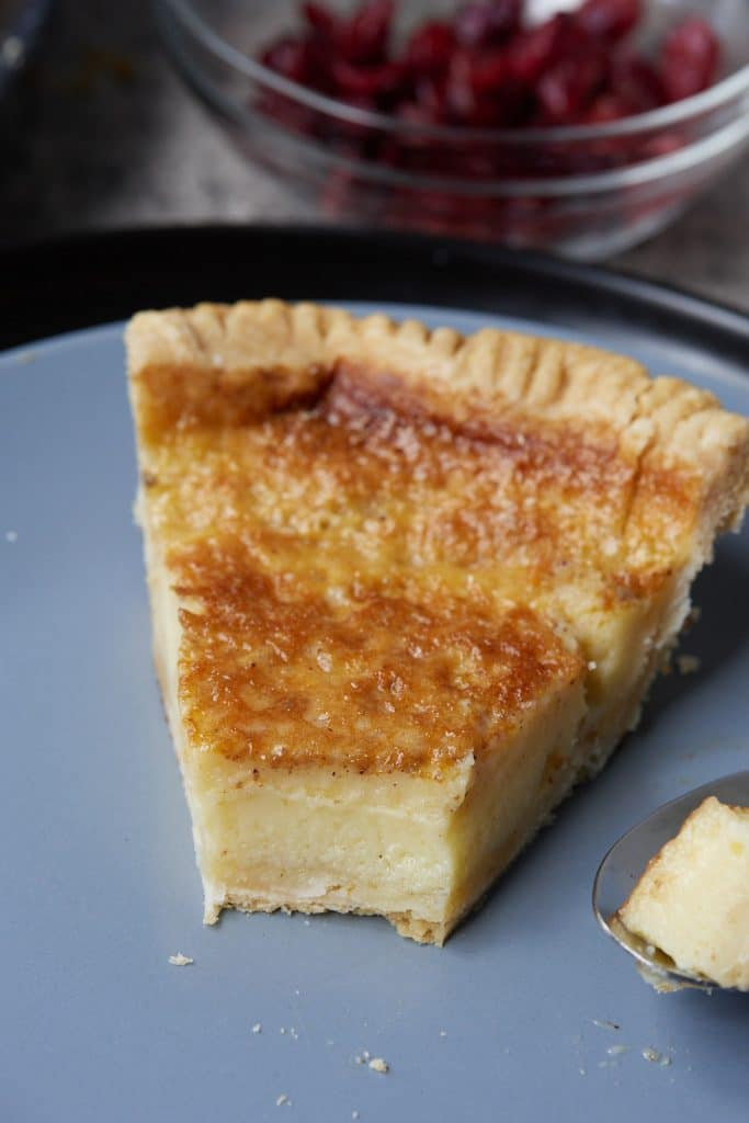 A slice of chess pie on a blue plate.